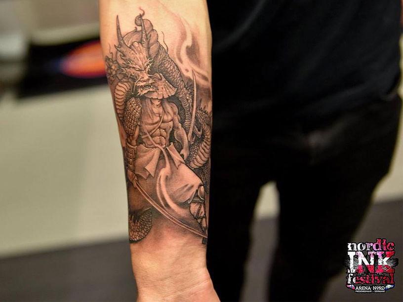 Samurai and dragon tattoo on arm at festival