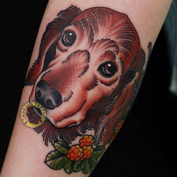 hình xăm con chó ở cánh tay mang lại may mắn cho các bạn nam tuổi kỷ tỷ